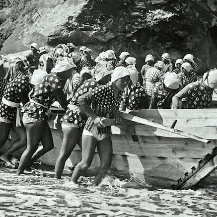 ca. 1947, Toba, Japan --- Pearl divers start to push their boats from the beach into Toba Bay. The young women harvest oysters implanted with pearls for the Mikomoto company. --- Image by © Horace Bristol/CORBIS